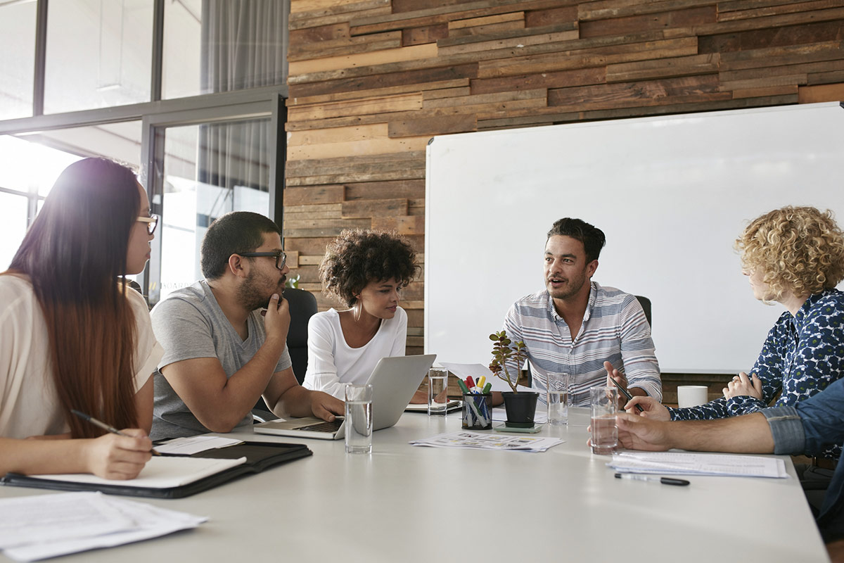 The 4Sight Group Blog How to Lead: Gender Issues in Leadership Team Sitting Around Table at Work